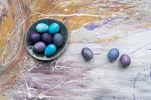 Painted chicken eggs in bowl and on
