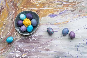 Colored Easter eggs in bowl and on s