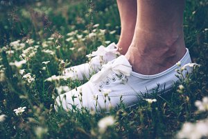 Woman in sneakers standing on meadow