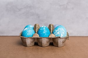 Painted eggs in egg carton on grey b