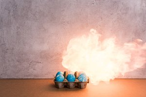 Painted eggs on fire on grey backgro