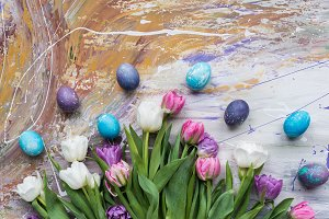 Colored eggs and tulips on stained b