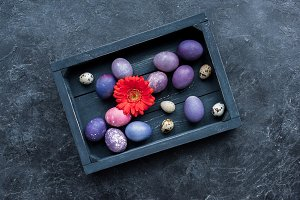 Box with painted eggs on dark backgr