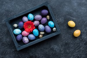 Box with painted eggs and flower on