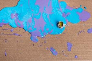 Broken quail egg in paint on cardboa