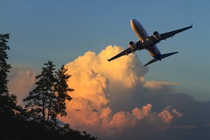 aircraft flying at sunset over the