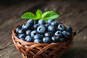 Blueberries in basket on rustic wood
