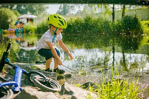 Boy plays with water near a lake