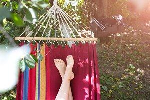 Girl is lying in colourful hammock