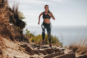 Woman running over rock trail