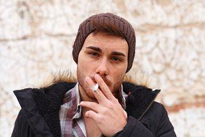 Sad guy with wool hat smoking a ciga