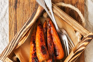 Baked carrots in a wooden box with p