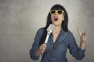 woman holding a microphone singing
