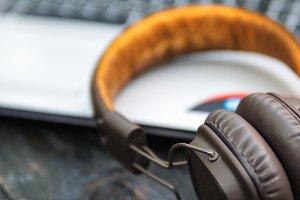 Headphones lie next to the laptop on