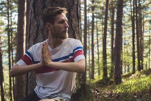 young bearded man meditating sitting