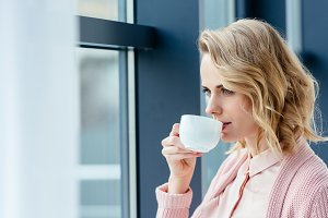 side view of thoughtful woman drinki