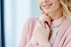 partial view of smiling woman in pin