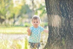 Little girl standing beside a tree