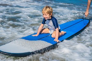 Happy baby boy - young surfer ride