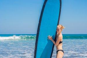 Surfer girl on the sandy beach