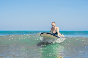 A woman learns to surf on the foam