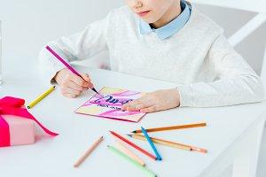 cropped shot of kid drawing greeting