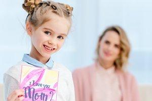 adorable daughter showing postcard o