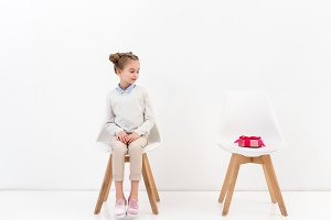 adorable child sitting on chair and