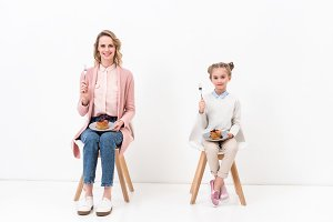 mother and daughter sitting on chair
