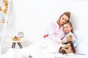 mother and daughter lying in bed wit