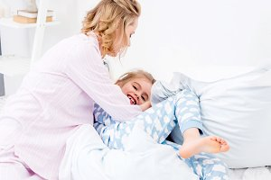 mother tickling daughter on bed at h