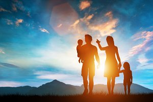 Happy family standing on a hill with