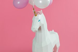 Toy unicorn under pink and white bal
