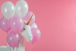 Toy unicorn among pink and white bal