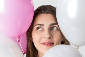 Smiling girl among balloons on white