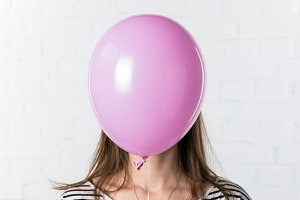 Pink balloon covering face of young
