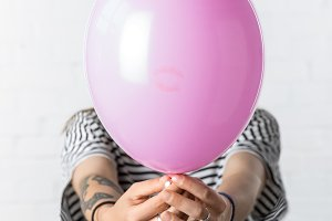 Girl holding pink balloon in front o