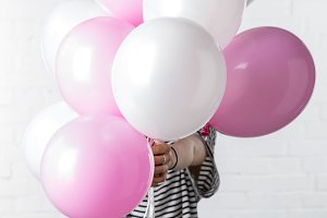 Woman holding pink and white balloon