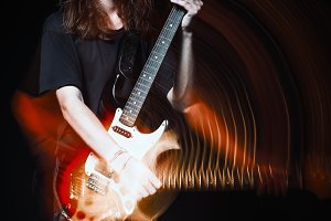 Long-haired young man with guitar