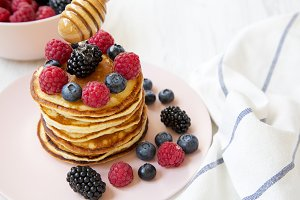 Tasty pancakes with berries and hone