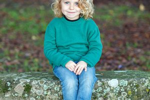 Beautiful child sitting on a bench i