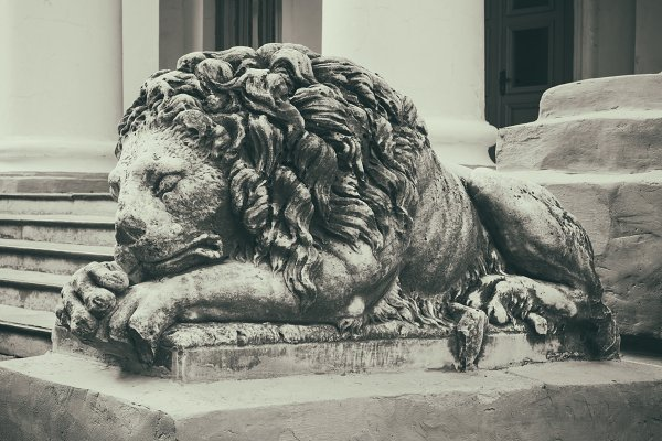Old vintage stone lion on steps.