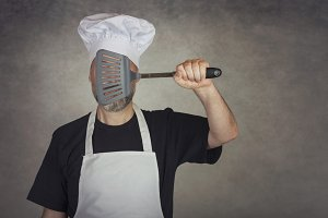 man holding spatula in his eyes
