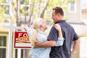 Caucasian Couple Faces Sold Sign
