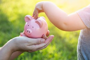 Woman Holds Piggy Bank While Baby Bo
