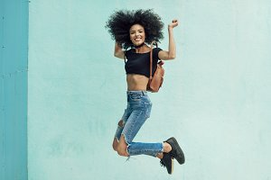 Young mixed woman with afro hair jum