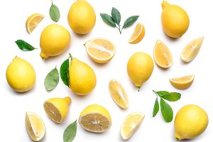 Ripe lemons and lemon leaves on whit