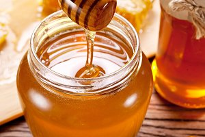 Honey flowing into glass can from wo