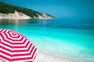 Striped red sun beach umbrella on a