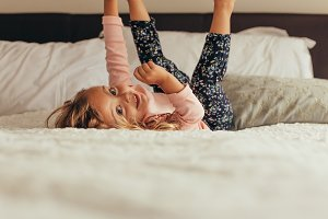 Little girl playing on bed